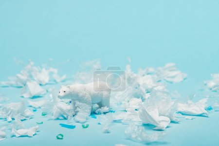 White toy polar bear with plastic garbage on blue background, animal welfare concept