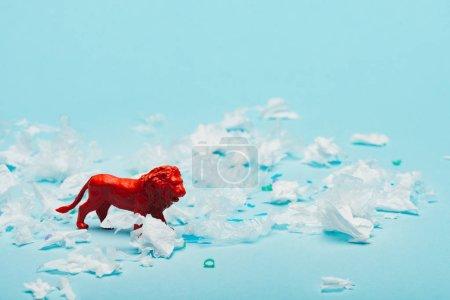 roter Spielzeuglöwe mit Plastikteilen auf blauem Hintergrund, Umweltverschmutzungskonzept