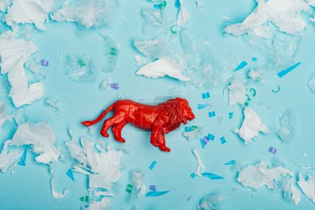 Top view of red toy lion with plastic garbage on blue background, environmental pollution concept