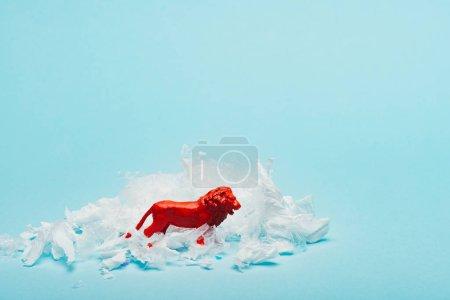 Photo pour Red toy lion with plastic garbage on blue background, animal welfare concept - image libre de droit