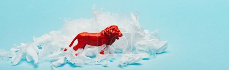 Photo pour Panoramic shot of red toy lion with plastic garbage on blue background, animal welfare concept - image libre de droit