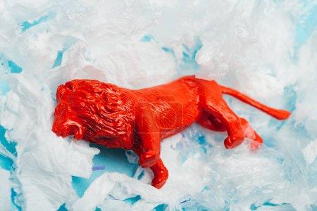 Photo pour Red toy lion on plastic garbage on blue background, animal welfare concept - image libre de droit