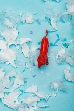 Top view of red toy lion on plastic garbage on blue background, animal welfare concept
