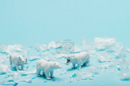 Photo for White toys of hippopotamus, rhinoceros and bear with plastic garbage on blue background, animal welfare concept - Royalty Free Image