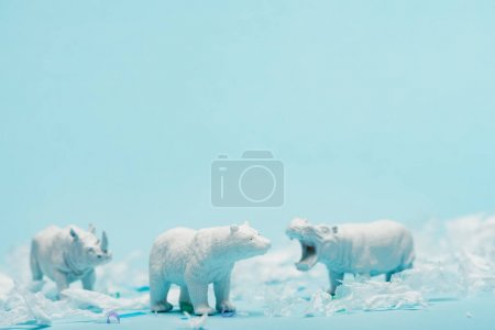 Photo pour White toys of hippopotamus, rhinoceros and bear with plastic garbage on blue background, animal welfare concept - image libre de droit