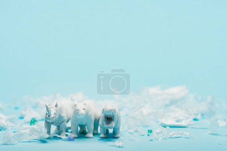 White toys of hippopotamus, rhinoceros and bear with plastic garbage on blue background, animal welfare concept