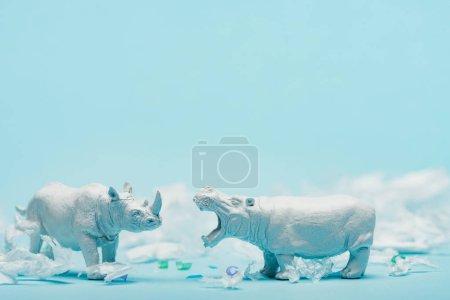 Photo pour Jouets hippopotame blanc et rhinocéros avec déchets en plastique sur fond bleu, concept de bien-être animal - image libre de droit