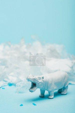 Photo pour Selective focus of hippopotamus toy with plastic garbage on blue background, animal welfare concept - image libre de droit