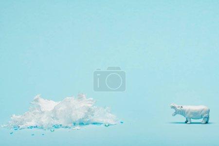 Photo pour White hippopotamus toy and plastic garbage on blue background, animal welfare concept - image libre de droit