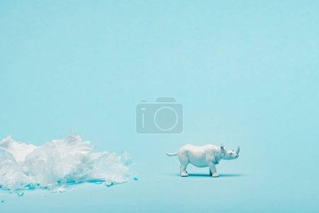 Photo pour Jouet à rhinocéros blancs et déchets en plastique sur fond bleu, concept de bien-être des animaux - image libre de droit
