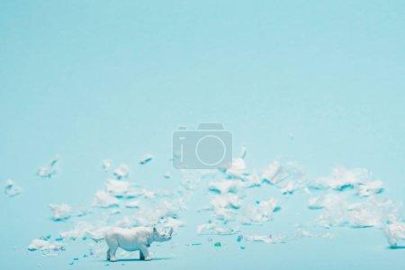 Foto de Juguete blanco de rinoceronte y basura plástica en fondo azul, concepto de contaminación medioambiental. - Imagen libre de derechos