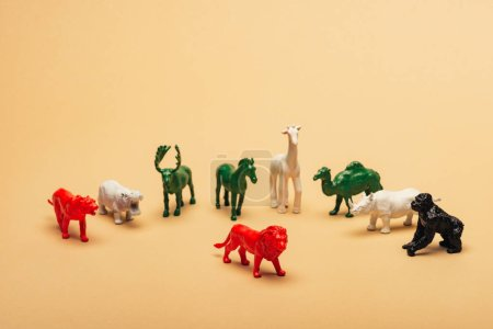 Photo pour Red lion with colored toy animals on yellow background, extinction of animals concept - image libre de droit