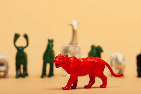 Photo pour Selective focus of red tiger with colored toy animals on yellow background, extinction of animals concept - image libre de droit