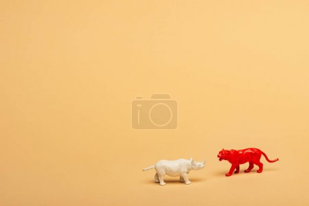 Photo pour Toy rhinoceros and tiger on yellow background, animal welfare concept - image libre de droit