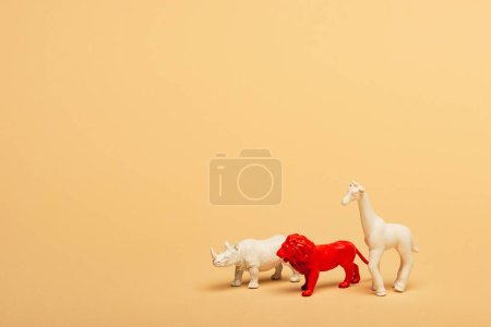 Photo pour Toy lion, rhinoceros and giraffe on yellow background, animal welfare concept - image libre de droit