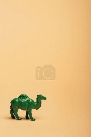 Photo pour Green toy camel on yellow background, animal welfare concept - image libre de droit