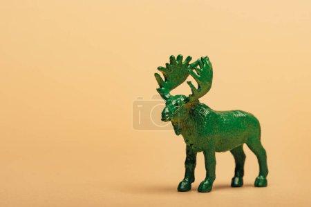 Зеленый игрушечный мак на желтом фоне, концепция защиты животных