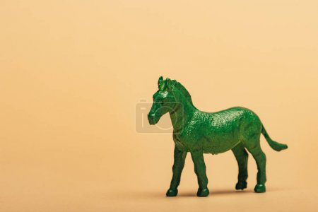 Photo pour Green toy horse on yellow background, animal welfare concept - image libre de droit