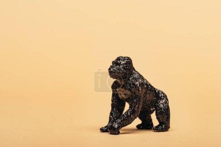 Photo pour Black toy gorilla on yellow background, animal welfare concept - image libre de droit