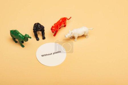 Photo pour Animaux jouets de couleur avec lettrage sans plastique sur carton sur fond jaune, concept de pollution environnementale - image libre de droit