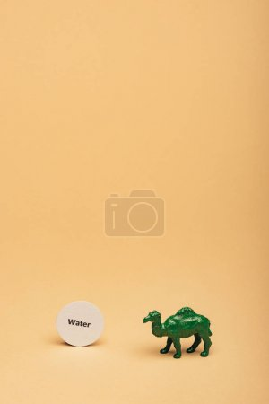 Photo pour Green toy camel with lettering water on card on yellow background, water scarcity concept - image libre de droit