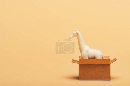 Photo pour Jouet girafe blanc dans une boîte en carton sur fond jaune, concept de bien-être animal - image libre de droit