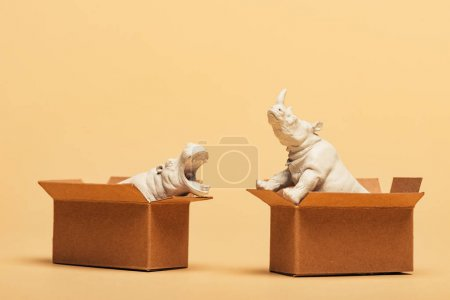 White toy hippopotamus and rhinoceros in cardboard boxes on yellow background, animal welfare concept