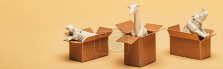 Panoramic shot of toy hippopotamus, rhinoceros and giraffe in cardboard boxes on yellow background, animal welfare concept