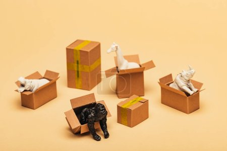 Photo pour Selective focus of animal toys in cardboard boxes on yellow background, animal welfare concept - image libre de droit