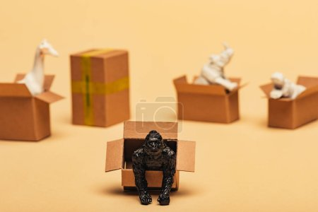 Selective focus of animal toys in cardboard boxes on yellow background, animal welfare concept