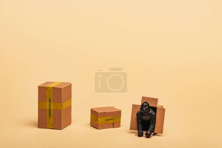 Toy gorilla in cardboard container with boxes on yellow background, animal welfare concept