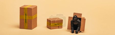 Panoramic shot of toy gorilla in cardboard container with boxes on yellow background, animal welfare concept
