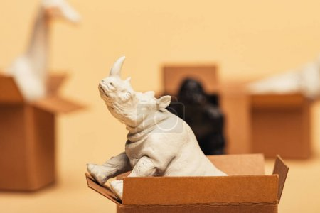 Photo pour Selective focus of rhinoceros and toy animals in cardboard boxes on yellow background, animal welfare concept - image libre de droit