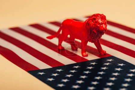 Photo pour Lion jouet rouge sur drapeau américain sur fond jaune, concept de bien-être des animaux - image libre de droit