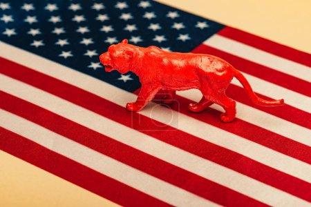 Photo pour Tigre rouge jouet sur drapeau américain sur fond jaune, concept de bien-être des animaux - image libre de droit