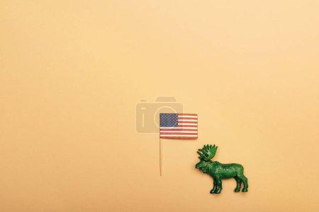 Вид сверху зеленого игрушечного болота с американским флагом на желтом фоне, концепция защиты животных
