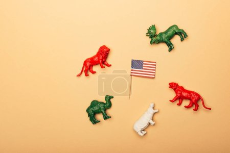 Photo pour Top view of toy animals with american flag on yellow background, animal welfare concept - image libre de droit
