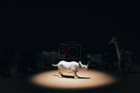 Photo pour Rhinocéros jouet blanc sous les projecteurs avec des animaux en arrière-plan, concept de vote - image libre de droit