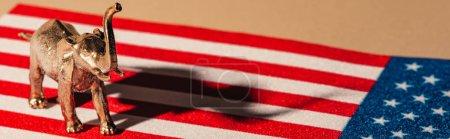 """Photo pour Photo panoramique d """"éléphant doré jouet avec ombre sur le drapeau américain, concept de bien-être des animaux - image libre de droit"""