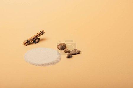 Photo pour Sand with stones and wooden sticks on yellow background, animal habitat concept - image libre de droit