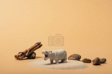 Photo pour Hippopotame jouet blanc avec des pierres et des bâtons de bois sur fond jaune, concept de bien-être animal - image libre de droit