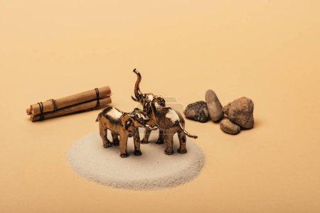 Photo pour Éléphants-jouets sur sable avec pierres et bâtons de bois sur fond jaune, concept de bien-être des animaux - image libre de droit