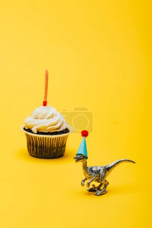 Foto de Toy dinosaur in party cap and cupcake with candle on yellow background - Imagen libre de derechos