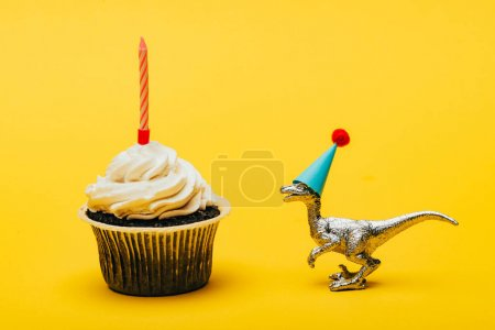 Photo for Toy dinosaur in party cap and cupcake with candle on yellow background - Royalty Free Image