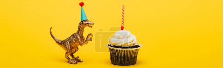 Photo for Panoramic shot of toy dinosaur in party cap and cupcake with candle on yellow background - Royalty Free Image