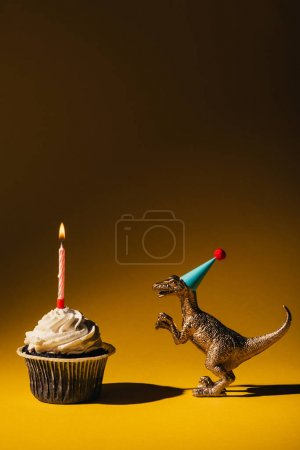 Photo for Toy dinosaur in party cap beside cupcake with burning candle on brown background - Royalty Free Image