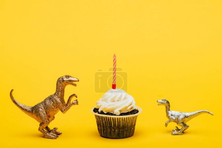 Foto de Toy dinosaurs beside cupcake with candle on yellow background - Imagen libre de derechos