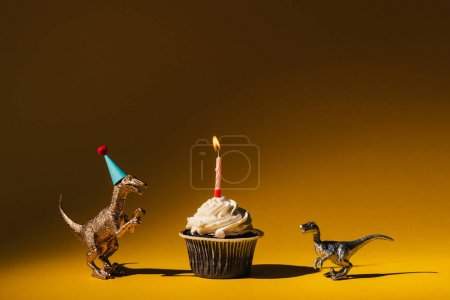 Photo for Toy dinosaurs with party cap and cupcake with burning candle on orange background - Royalty Free Image
