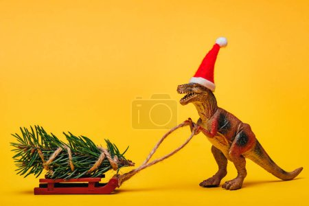 Toy dinosaur in santa hat with pine on sleigh on yellow background