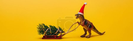 Panoramic shot of toy dinosaur in santa hat with pine on sleigh on yellow background